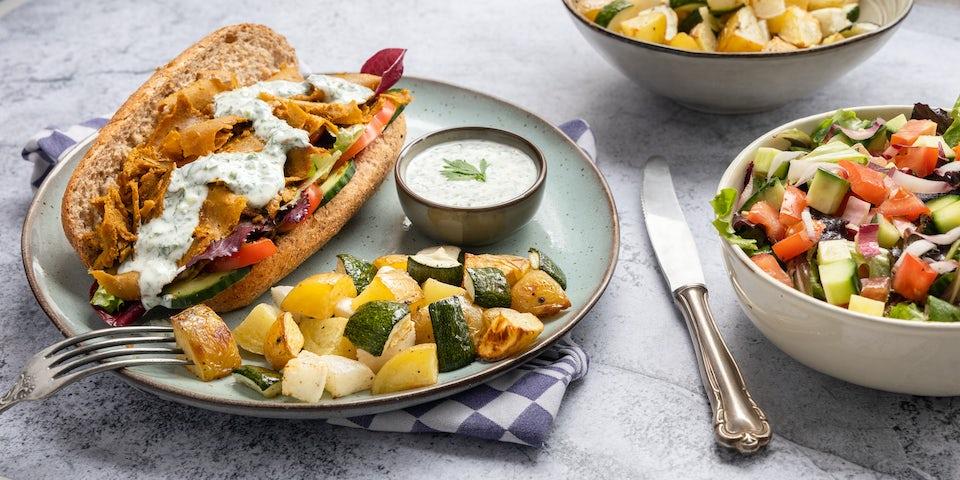 Brioche met vegan kebab knoflooksaus geroosterde aardappelen en meiraap en een salade