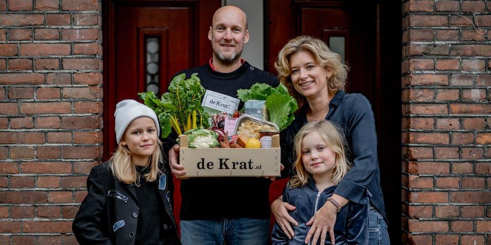 Een gezin met kinderen houden een maaltijdbox met lokale producten vast