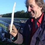 De teler van Zuyderzee asperges houdt een asperge vast op het boerenland