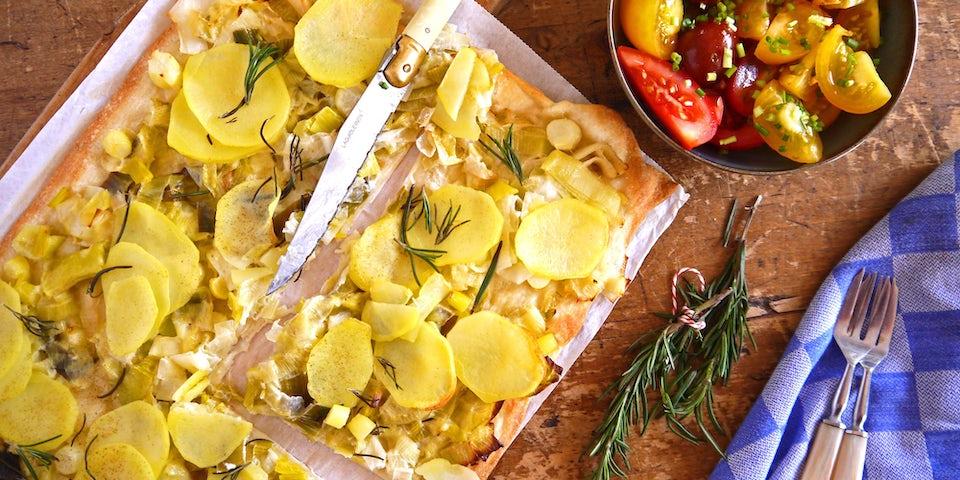 3050 Flammkuchen Met Prei Aardappel En Rozemarijn Met Salade Van Gekleurde Tomaten