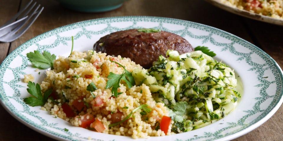3746 Merguezburger Met Frisse Courgette Salade En Couscous Met Tomaat En Groene Kruiden