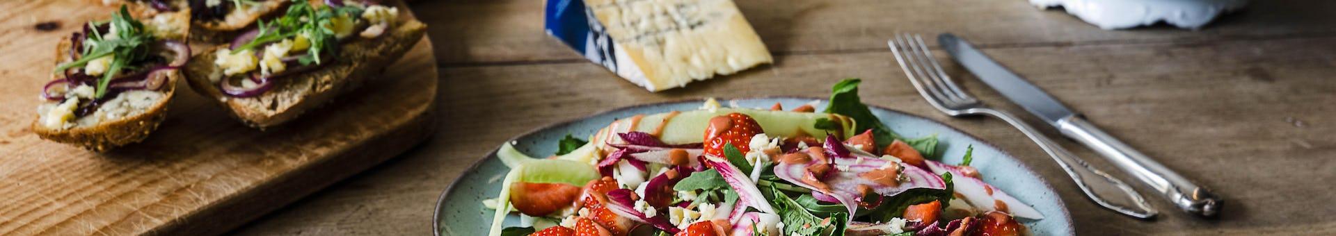 Gezonde aardbei salade met broodjes en kaas op de achtergrond