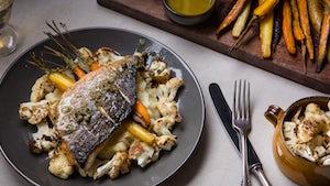Duurzame vis: dorade filet met aardappel aardpeerpuree geroosterde bloemkool peen op een bord